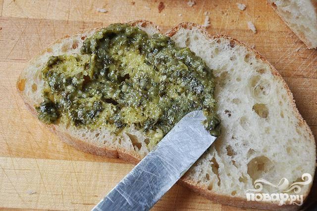 2. Ложкой выложить на ломтики хлеба соус Песто и равномерно распределить по всей поверхности.
