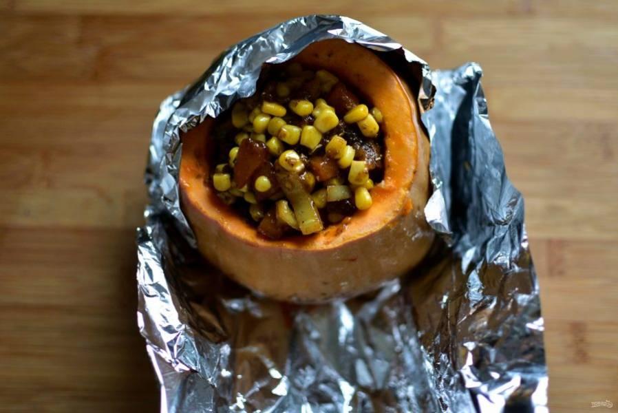 Выложите рагу в тыкву, заполняя ее доверху. Влейте бульон со сковороды и добавьте немного воды, если нужно, чтобы уровень жидкости был немного ниже края тыквы. Заверните тыкву в фольгу и отправьте в разогретую до 180 градусов духовку, запекайте до мягкости тыквы.