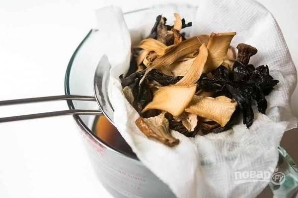 Сушеные грибы хорошо промываем, затем заливаем их горячей водой на 30 минут, отцеживаем воду.