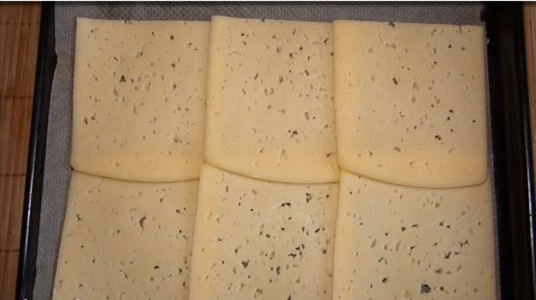 Выкладываем пластики сыра на противень, застеленный листом пергамента. Сырные листики должны чуть-чуть заходить друг на друга.