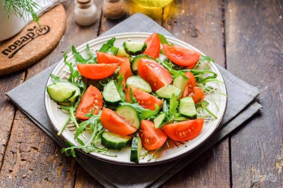Свежие помидоры нарежьте дольками, также нарежьте огурцы. Выложите овощи поверх рукколы.