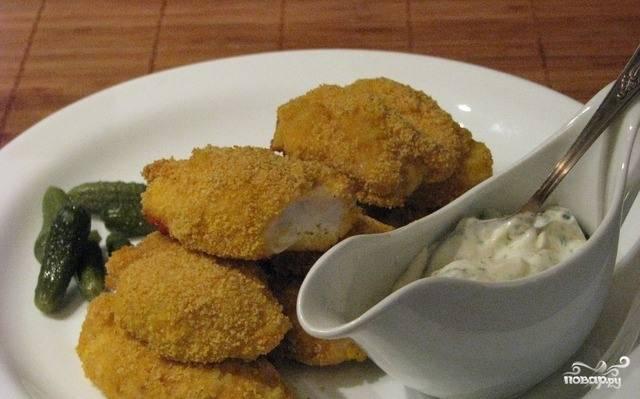 Для соуса смешайте нарезанный огурец с майонезом. Подавайте наггетсы ещё горячими. Приятного аппетита!