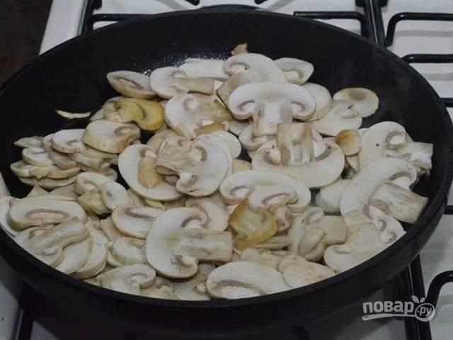 Промойте и нарежьте пластинками шампиньоны. Обжарьте их до испарения жидкости в сковороде с маслом.