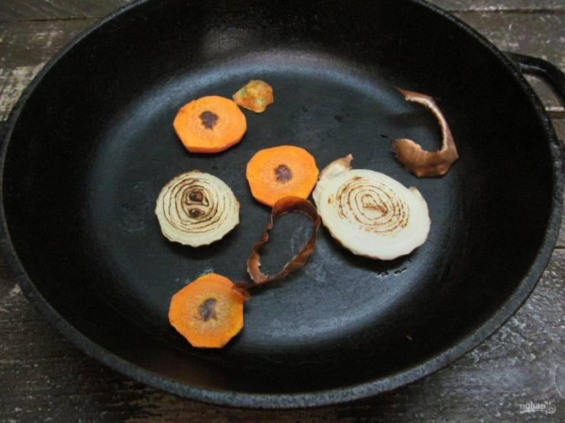 Нарежьте лук и морковь толстыми кольцами. Обжарьте на сухой сковороде до горелых вкраплений.