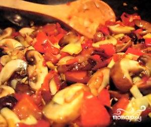 К луку добавить подготовленные морковь и перец. Обжаривать 5 минут. Следом добавить нарезанные шампиньоны. Тушить до тех пор, пока жидкость не выпарится.