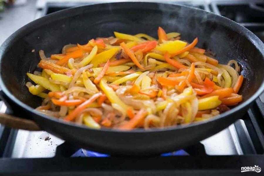 Лук порежьте кольцами или полукольцами. Перец порежьте соломкой. Разогрейте на сковороде растительное масло,  сначала обжарьте в нём лук, а потом добавьте перец. Обжаривайте, пока перец и лук не подрумянятся и не станут мягкими.