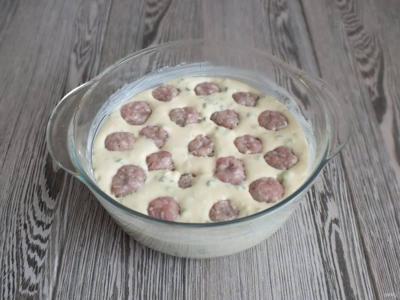 Форму с бортами смажьте обильно маслом, вылейте тесто. Фрикадельки слегка вдавите в тесто. Духовку разогрейте до 180 градусов и поставьте выпекаться пирог на 25 минут.