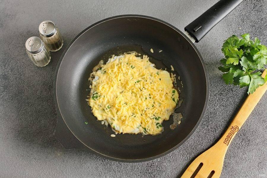 Посыпьте яйцо тертым сыром.