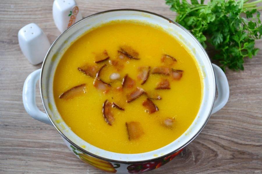 Следом за сыром отправьте в суп шкварки. Перемешайте, проварите пару минут и снимите кастрюлю с огня.