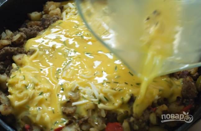 Заливаем яичной смесью овощи с фаршем и жарим все до готовности яиц и испарения жидкости.