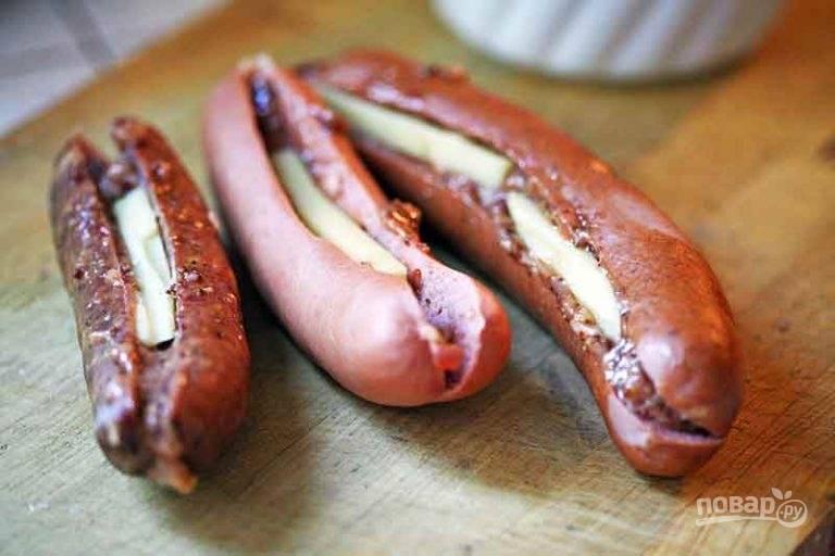 1.Смешайте горчицу, кетчуп. В другой миске смешайте квашеную капусту, измельченный лук. Возьмите длинные сосиски и сделайте надрез от одного края до другого, но не прорезая полностью. Смажьте смесью горчицы и кетчупа, выложите внутрь тонкие ломтики сыра.