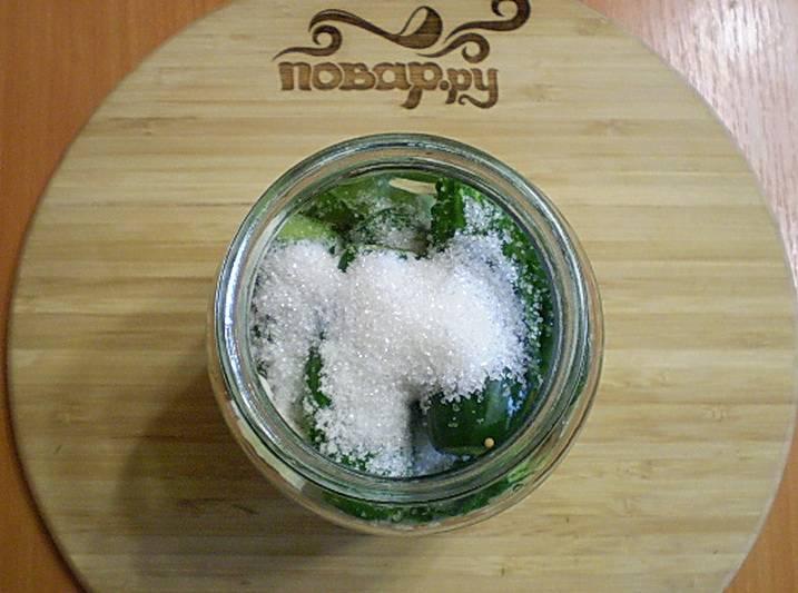 Плотно уложите в банку огурцы. Насыпьте соль и сахар.