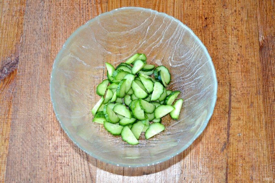 Огурцы нарежьте тонкими ломтиками и выложите в глубокий салатник.