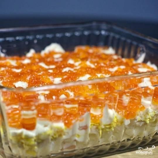Сверху украшаем салат красной икрой. Ставим в холодильник на несколько часов, после чего подаем. Салат слоеный с креветками готов!
