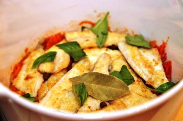 Затем выложите в кастрюлю слоями кусочки филе и овощи. На второй слой рыбы положите перец горошком и лавровый лист.