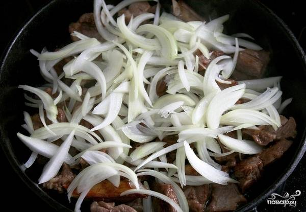 Когда мясо подрумянится - добавляем в сковороду средними кусочками нарезанный лук и болгарский перец.