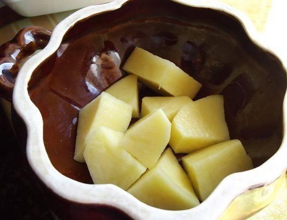 Картошку чистим и нарезаем довольно большими кубиками. Раскладываем по горшочкам. Данное количество продуктов рассчитано на 6 горшочков.