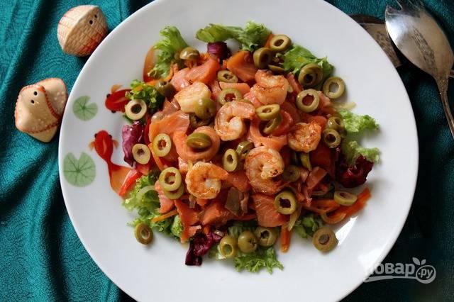 Поверх овощей выложите кусочки красной рыбки, обжаренные креветки и кружочки оливок. В качестве соуса можно использовать масло, в котором жарились креветки и овощи.