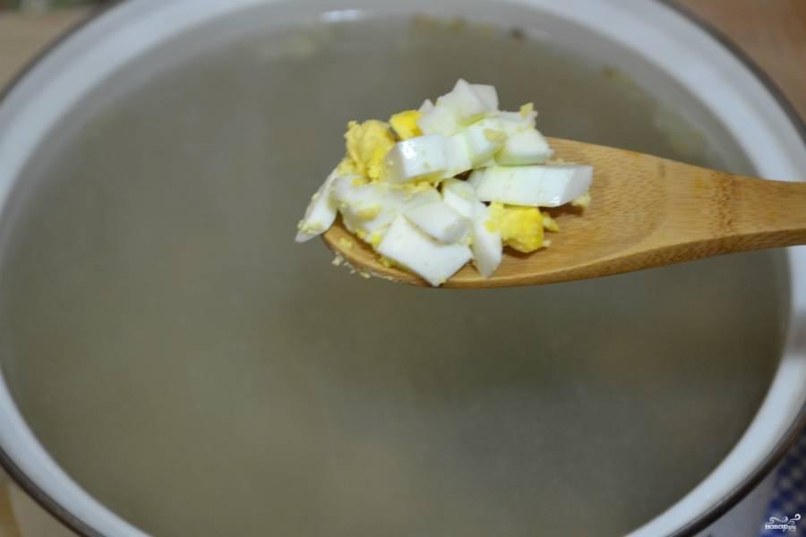 Отваренные вкрутую яйца измельчите и отправьте в суп. Варите до готовности всех ингредиентов.