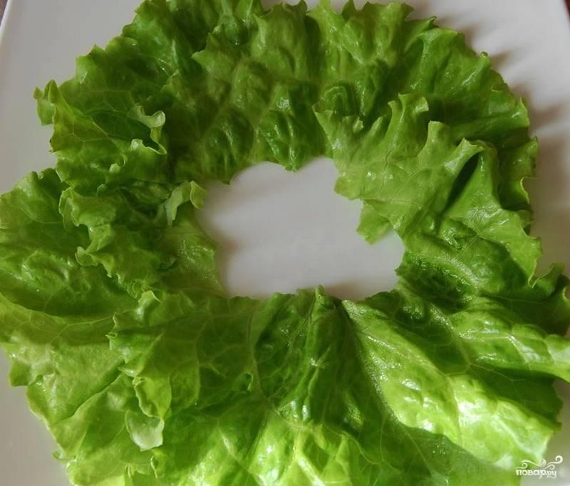 Салат хорошо вымойте. Удалите жёсткие стебли и хорошо просушите листья. Выложите часть салата кругом на тарелку, сформировав таким образом подложку для подачи блюда.