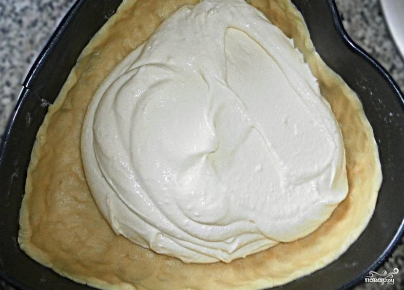 Извлекаем тесто из холодильника, укладываем его в разъемную форму, сформировав бортики. Перемешиваем в блендере: сахар, творог, желтки, манку и ваниль. Выкладываем на тесто творожную начинку.