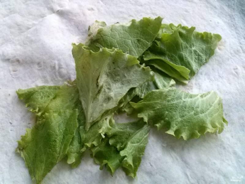 Порвите  чистые салатные листья руками, выложите их на лаваш.