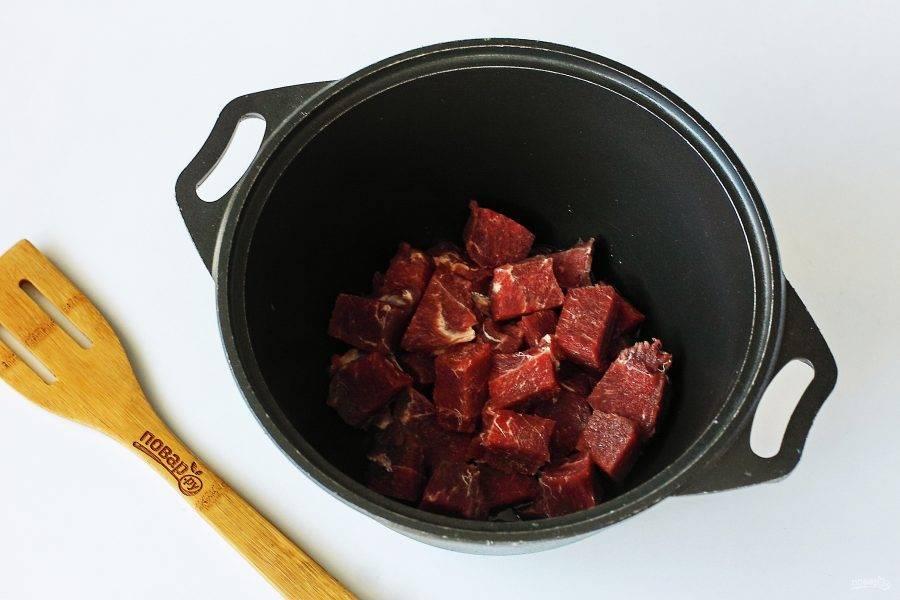 Мясо нарежьте небольшими кусочками и переложите в казан или любую другую посуду с толстым дном.
