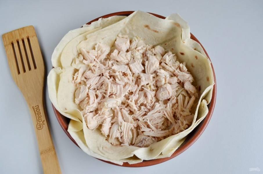 Порежьте куриное филе на крупные кусочки. Распределите по дну пирога.