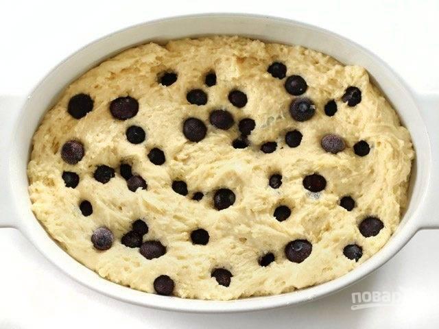 7.Смажьте форму для выпечки маслом, выложите в нее тесто и уткните замороженные ягоды черники.