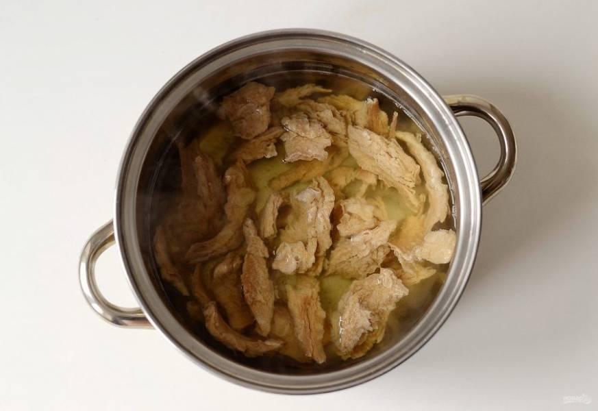 Добавьте в процеженный овощной бульон соль по вкусу. Отварите в нем соевый текстурат до мягкости. Затем тщательно отожмите кусочки.