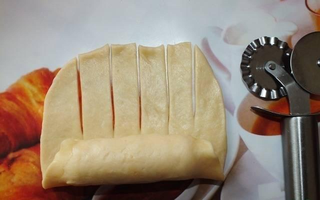 Начинаем формировать булочку. Заворачиваем сосиску с неразрезанного края.