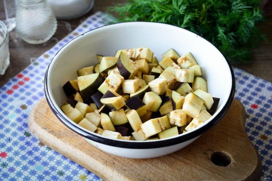 Баклажаны промойте и нарежьте средними кубиками. Присыпьте солью и оставьте в таком виде на 15 минут на столе. Уйдет горечь из баклажанов.