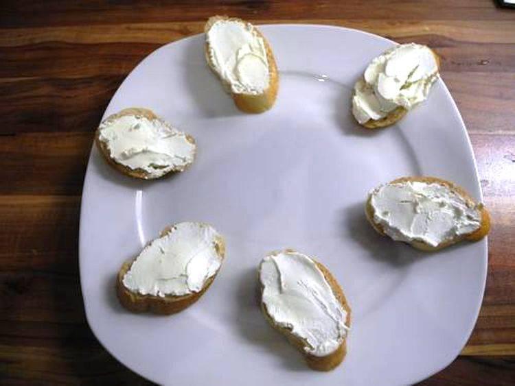 Порежьте багет и намажьте каждый ломтик мягким сыром.