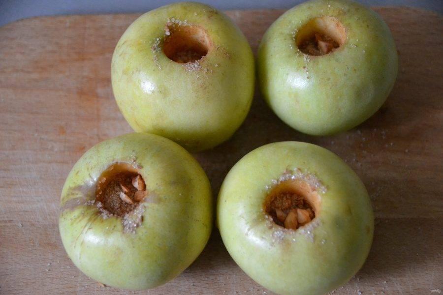 Заполните сахарно-ореховой смесью выемки у яблок.