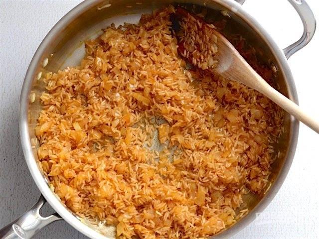 3.Выложите в сковороду сырой рис, перемешайте хорошенько и готовьте 1-2 минуты.
