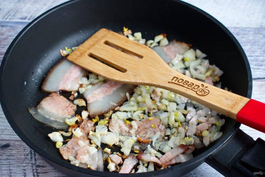 На сковороде разогрейте оливковое масло. Часть бекона нарежьте тонкими полосками. Измельченный лук пассеруйте до прозрачности, ломтики бекона - до хрустящей корочки.