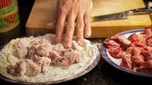 1. В широкую тарелку всыпьте муку, добавьте соль и перец, перемешайте. Свинину порежьте крупными кубиками, срежьте пленочки и обваляйте в мучной смеси.