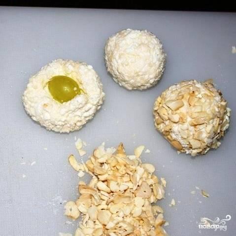 Теперь ключевой момент. Из творожной массы формируем шарики, внутрь каждого из которых кладем мытую виноградинку. Заворачиваем шарик, обваливаем его в ореховой крошке - и ставим в холодильник еще на 10-20 минут.