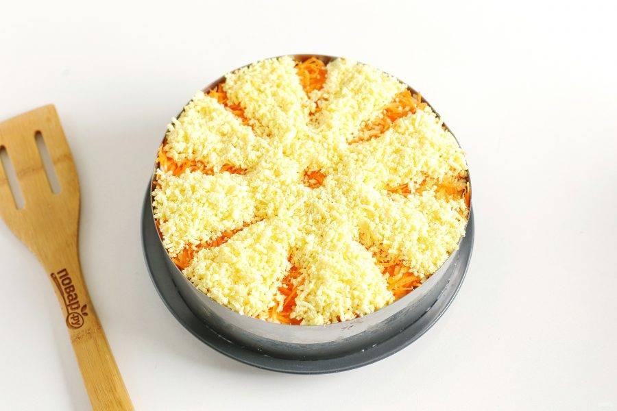 В завершении сделайте слой из моркови и тертых желтков. Чтобы верхушка салата смотрелась красивее, компоненты можно выложить полосками. Салату дайте 1 час для пропитки в холодильнике, потом подайте его на стол.