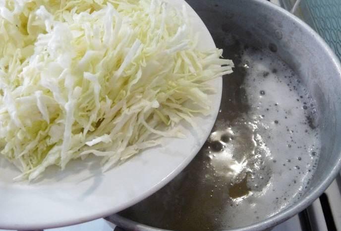 Когда бульон в кастрюле снова закипит, выкладываем в него нашинкованную капусту, варим ее минут 5-6.