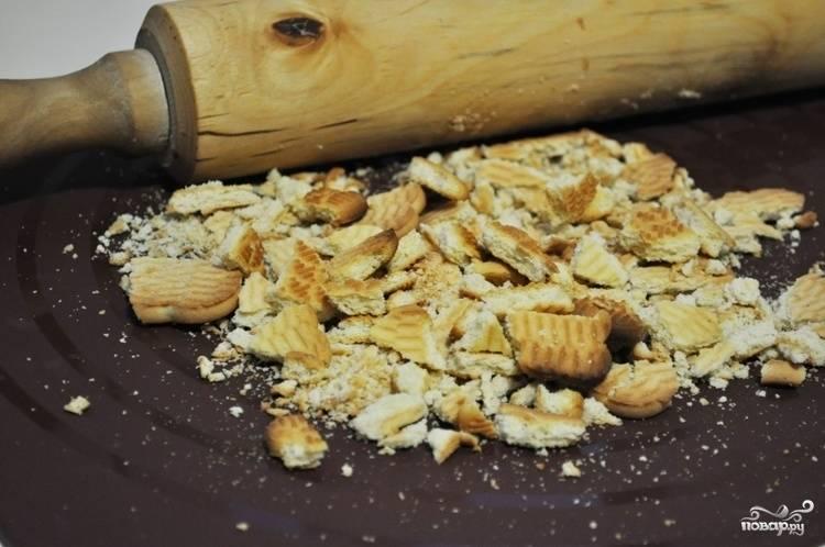 Для начала выложите печенье на рабочую поверхность. Его нужно превратить в крупную крошку. Можете делать это руками или скалкой. Таким же образом измельчите грецкий орех.