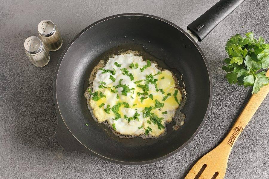 В сковороде растопите кусочек сливочного масла (огонь должен быть небольшой). Разбейте яйцо и сразу же лопаткой нужно аккуратно распределить яйцо по сковороде, так, чтобы желток тоже растёкся. Необходимо довести размер яичной лепешки по площади до размера двух кусочков хлеба, с которым вы будете дальше готовить. Яйцо посолите, поперчите и посыпьте рубленой зеленью.