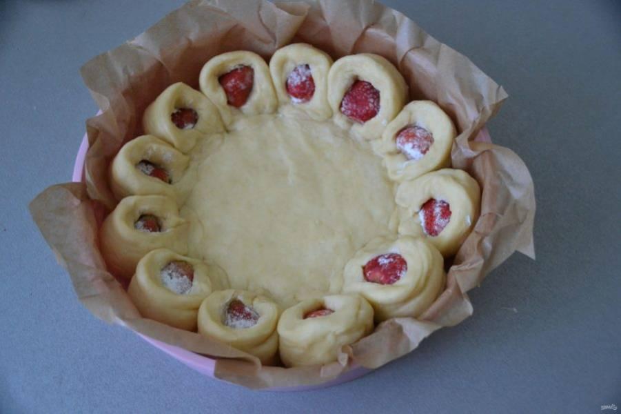 Закрепите один край разреза, переверните его на 90 градусов и разверните другой срез, чтобы клубника была наружу. Перенесите пирог прямо на пергаменте в форму для выпечки.