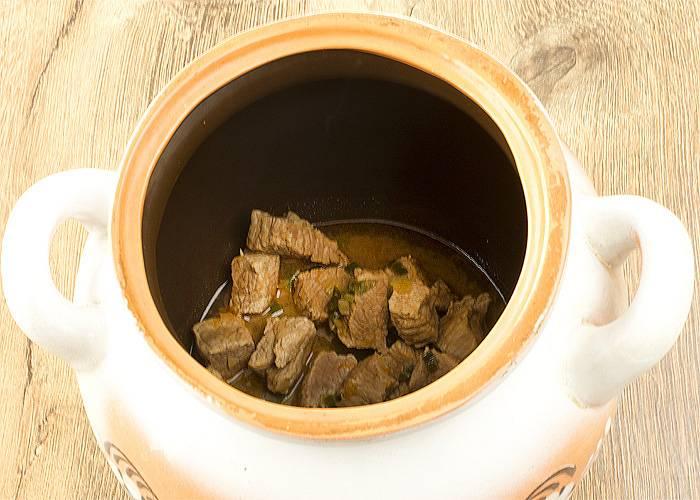 В горшочек кладем немного масла или жира, измельченный лук и нарезанное мясо. Добавляем немного воды и отправляем в духовку при 180 градусах на 30 минут.