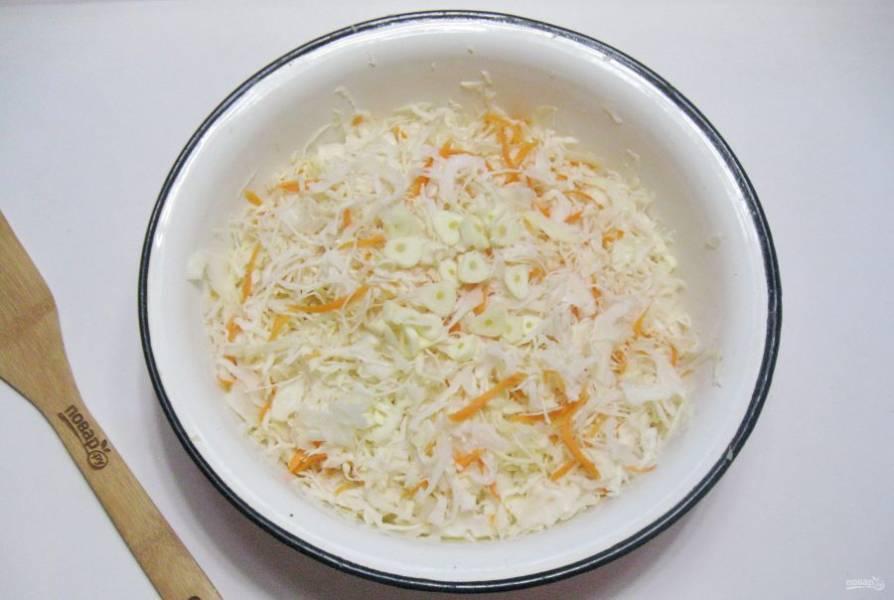 Зубчики чеснока нарежьте и добавьте в капусту с морковью.
