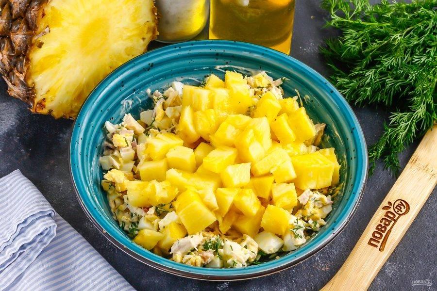 Последним нарежьте ананас (свежий или консервированный), оставьте нарезку на 5 минут, чтобы из нее выделился сок, а затем добавьте в емкость. Аккуратно перемешайте салат.