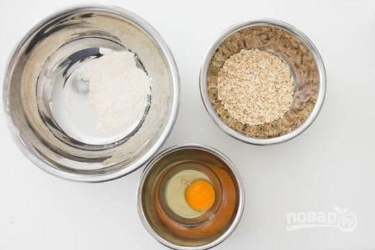 1.Подготовьте три миски: одну — с мукой, вторую — с овсяными хлопьями, а в третью разбейте и перемешайте яйцо. Почистите бананы.