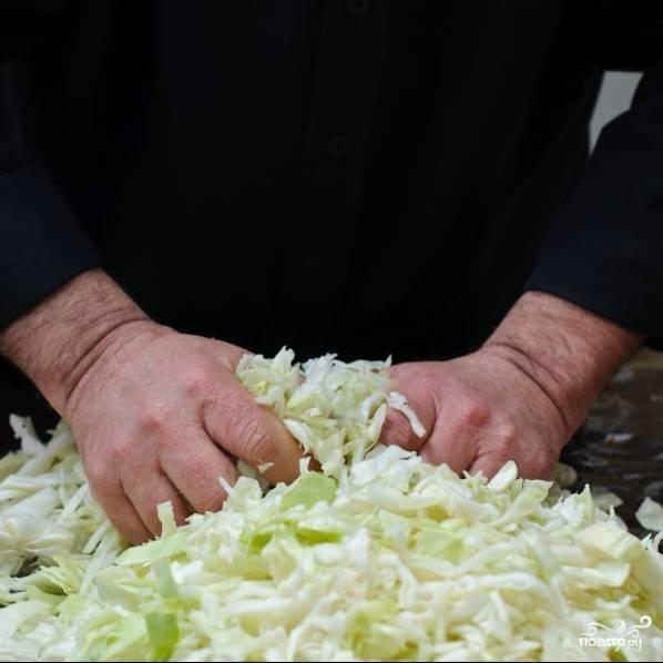 Хорошенько перетираем (перемешиваем) капусту руками. Это - мужское дело, поскольку капусту нужно довольно крепко сжимать руками, чтобы она стала выпускать жидкость, необходимую для процесса ферментации. Впрочем, опытные женские руки тоже способны справиться с этой задачей.