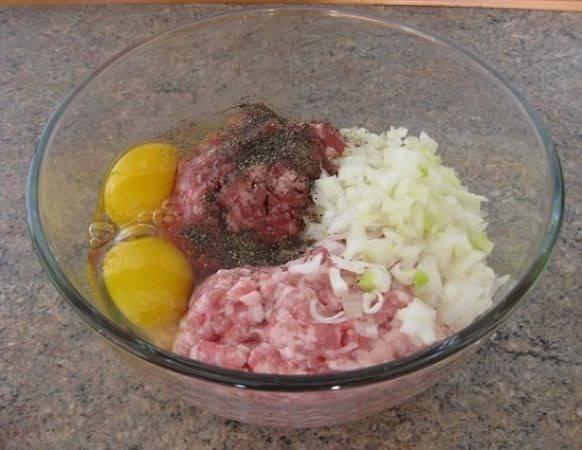 Ставим в предварительно разогретую духовку на 20 минут с температурой 180 градусов. Теперь приготовим начинку для нашего рулета. Смешиваем два вида фарша: говяжий и свиной. Мелко нарезаем одну крупную или две небольшие луковицы. Добавляем лук в фарш, туда же два яйца. Солим и перчим по вкусу.