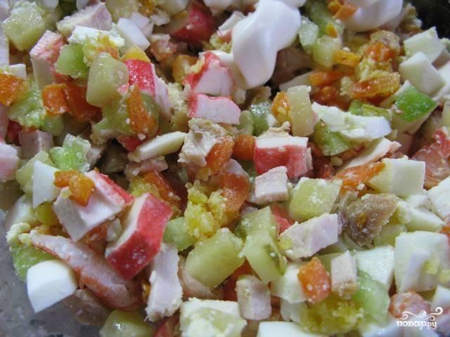 Мелко порубите все ингредиенты для салата: варёные морковь, яйца и креветки, крабовые палочки, маринованные огурцы. Перемешайте с майонезом. Добавьте ваших любимых специй, посолите по вкусу и снова перемешайте.